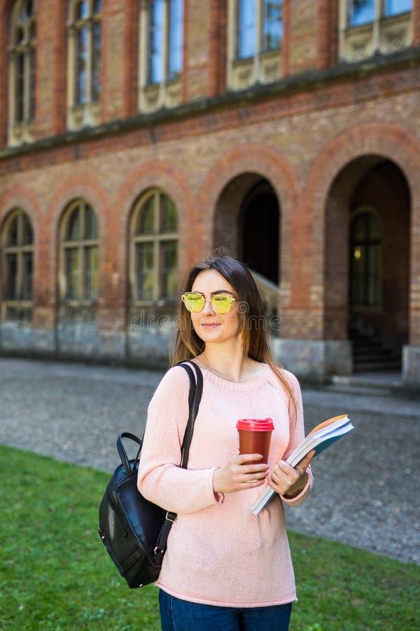 Estudiante universitario que sonríe con café y la bolsa de libros en campus con el espacio de la impresión fotos de archivo