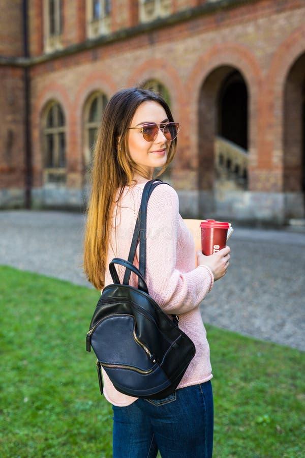 Estudiante universitario que sonríe con café y la bolsa de libros en campus con el espacio de la impresión foto de archivo