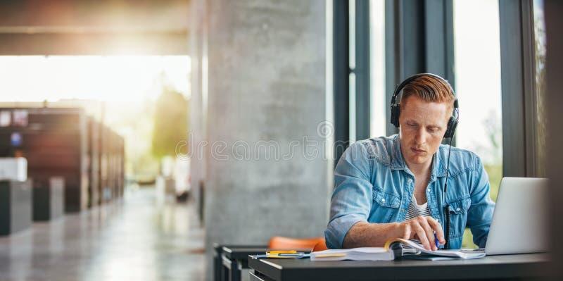 Estudiante universitario que trabaja en la asignación académica imagen de archivo libre de regalías