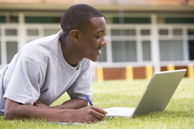 Estudiante universitario que usa la computadora portátil en césped del campus imagenes de archivo