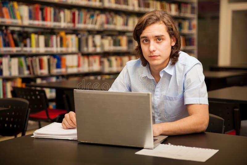 Estudiante universitario que usa una computadora portátil imagen de archivo libre de regalías