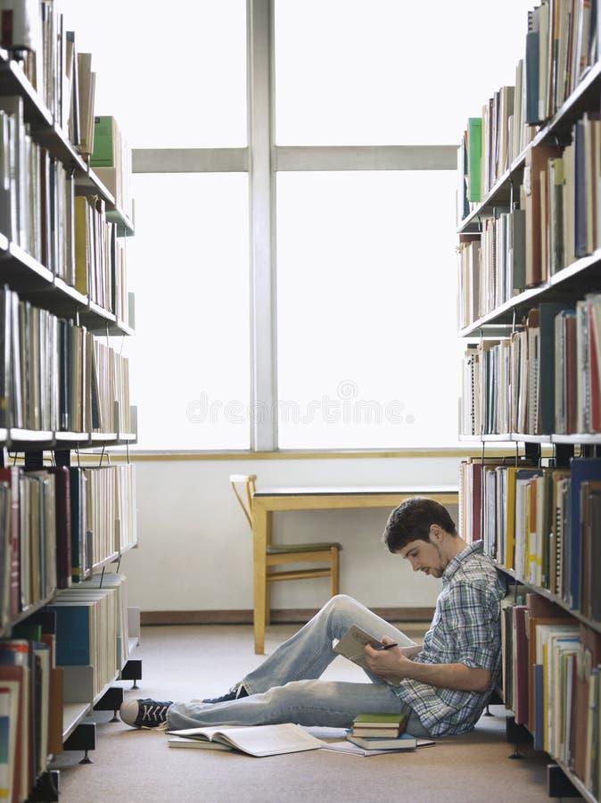 Estudiante universitario Reading In Library foto de archivo