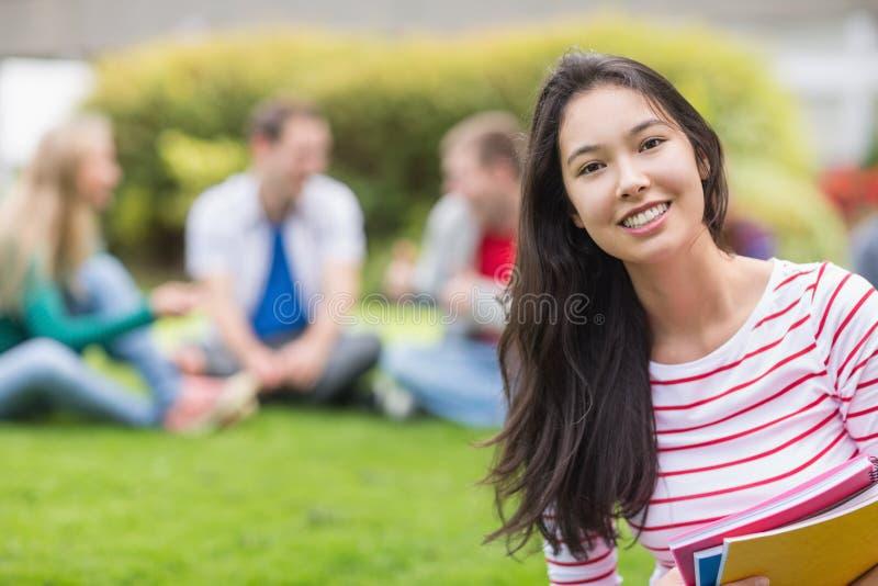 Estudiante universitario sonriente con los amigos borrosos en el parque imágenes de archivo libres de regalías