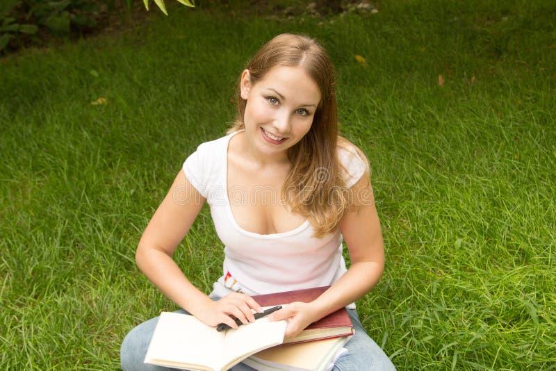 Estudiante universitario sonriente que lee un libro fotografía de archivo