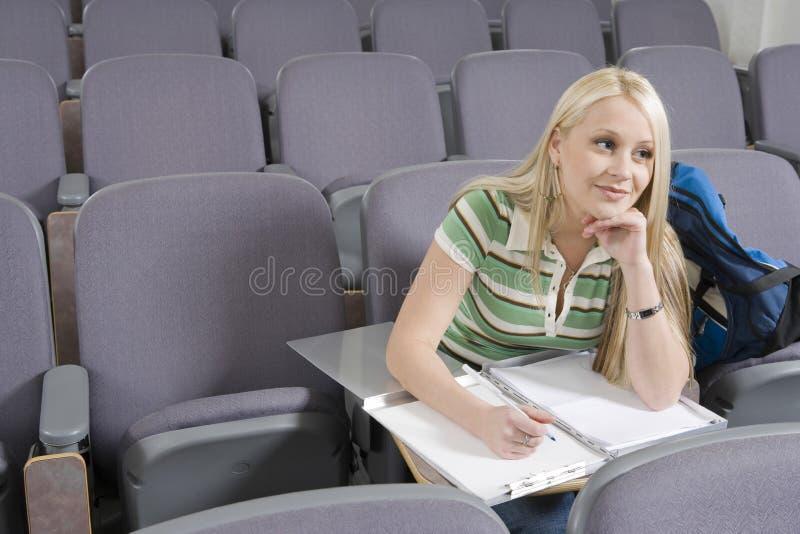 Estudiante universitario Writing In Lecture Pasillo imagen de archivo libre de regalías