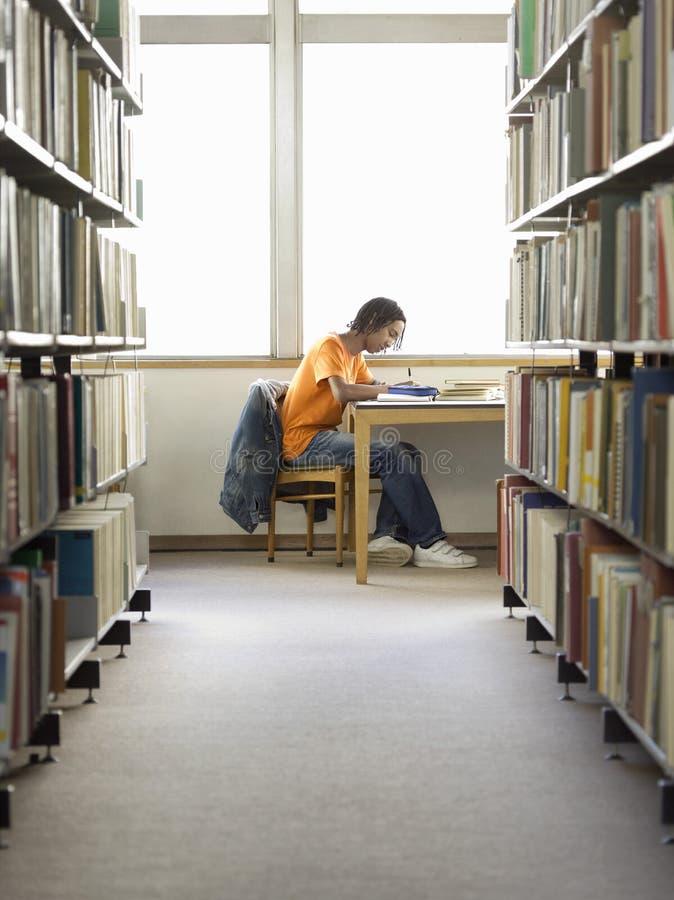 Estudiante universitario Writing In Library imagen de archivo