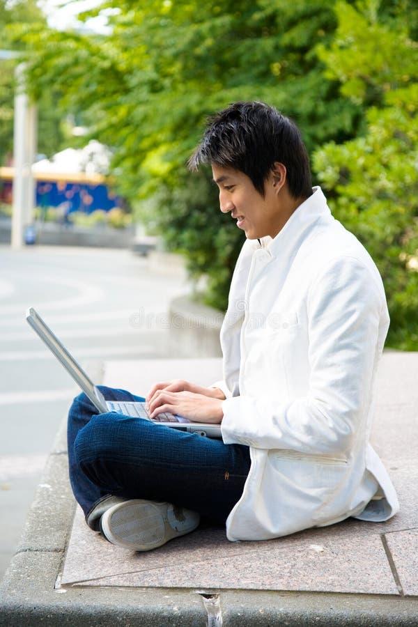 Estudiante universitario y computadora portátil asiáticos fotos de archivo libres de regalías