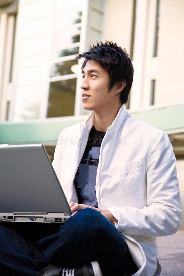 Estudiante universitario y computadora portátil asiáticos imagen de archivo