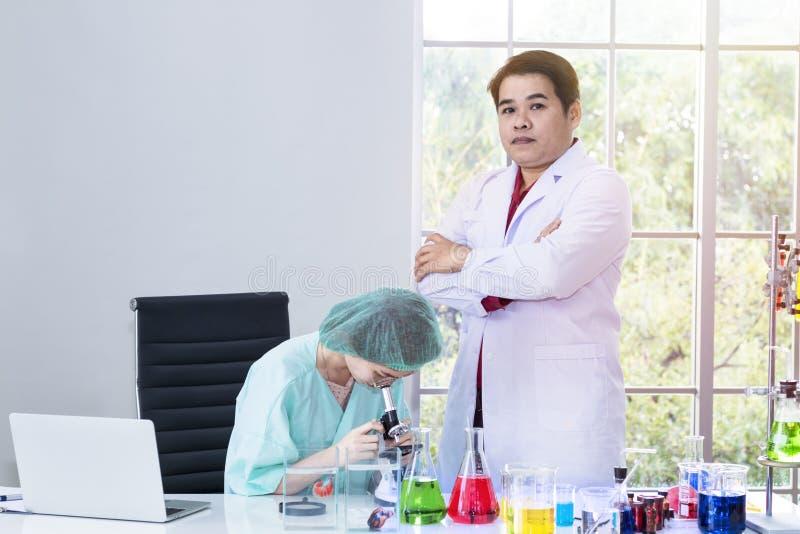 Estudiante veterinario de la mujer que mira a través de un microscopio cerca del tubo de ensayo imagen de archivo libre de regalías
