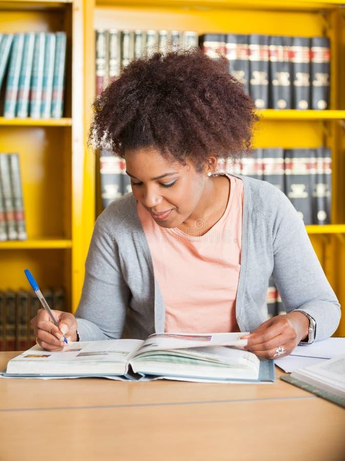 Estudiante Writing In Book en la biblioteca foto de archivo libre de regalías