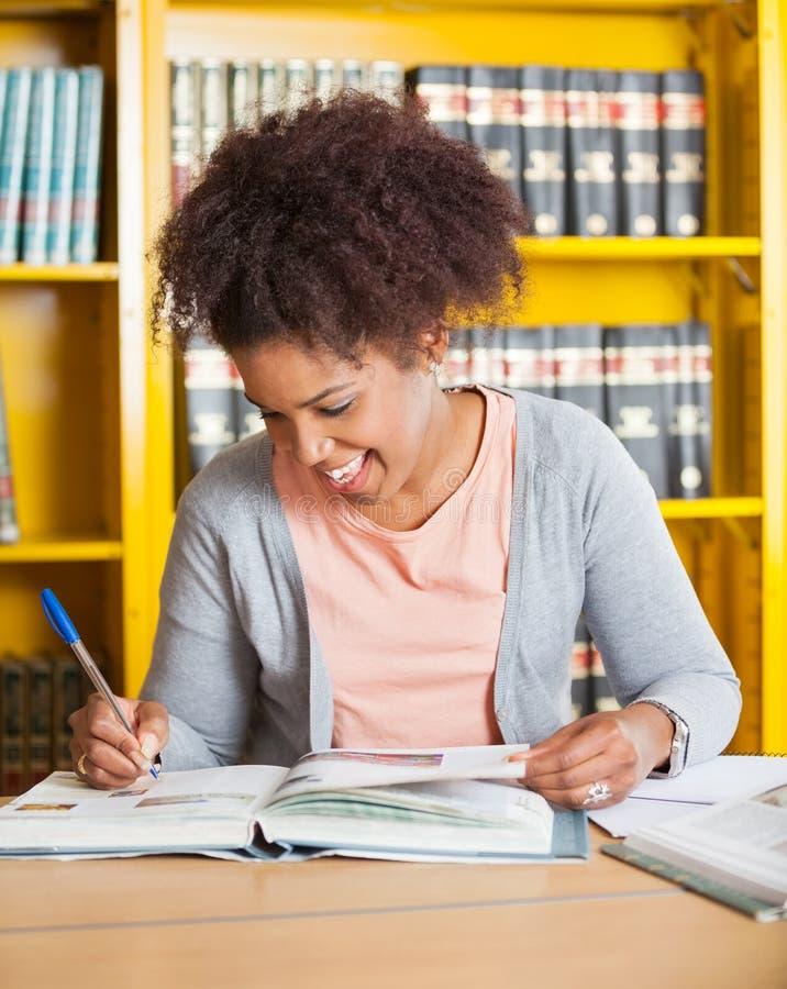 Estudiante Writing In Book en la biblioteca de universidad fotografía de archivo