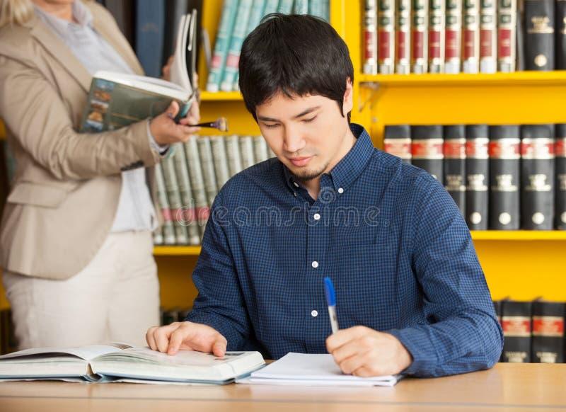 Estudiante Writing In Book en la biblioteca de universidad fotos de archivo libres de regalías