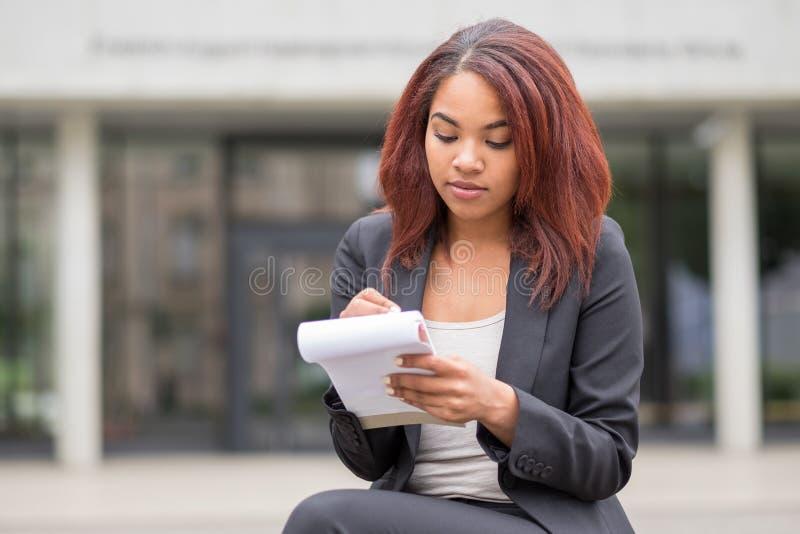 Estudiante Writing Notes Outside del negocio la escuela fotografía de archivo