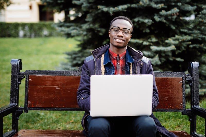 Estudiante y trabajo alegres africanos jovenes del hombre sobre el ordenador portátil que se sienta en el banco en la calle al ai fotos de archivo