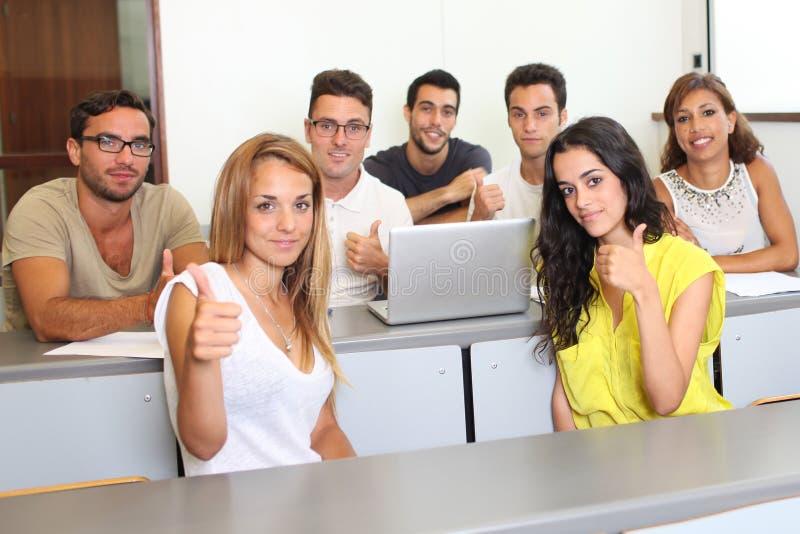 Estudiantes acertados que detienen los pulgares imagen de archivo