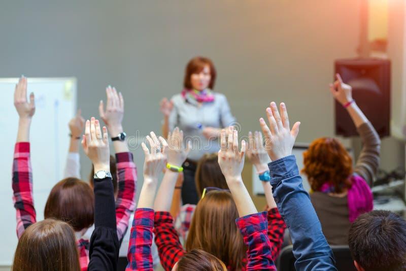 Estudiantes activos que aumentan los brazos encima de listo para contestar a la pregunta de los profesores imagen de archivo
