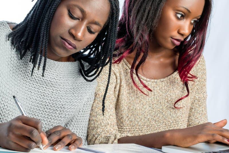 Estudiantes adolescentes africanos que trabajan junto en el escritorio fotos de archivo libres de regalías