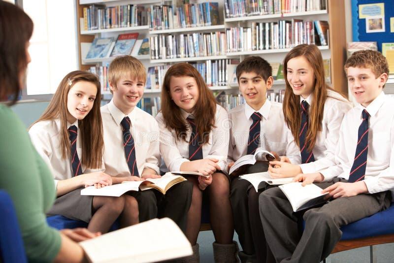Estudiantes adolescentes en libros de lectura de la biblioteca foto de archivo libre de regalías