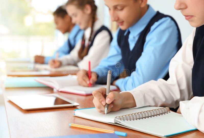 Estudiantes adolescentes en uniforme escolar elegante en el escritorio, imagen de archivo