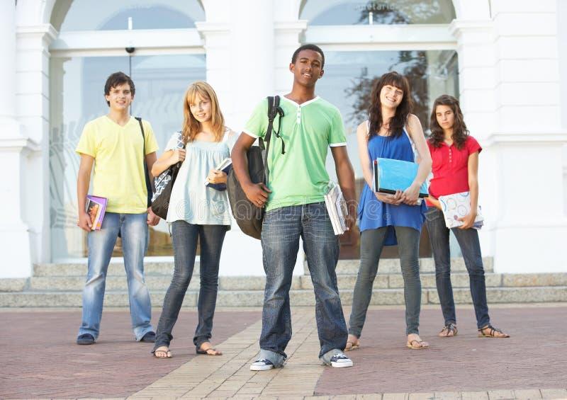 Estudiantes adolescentes que colocan el edificio exterior de la universidad imagen de archivo libre de regalías