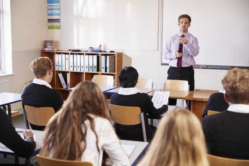 Estudiantes adolescentes que escuchan el profesor de sexo masculino In Classroom imagenes de archivo