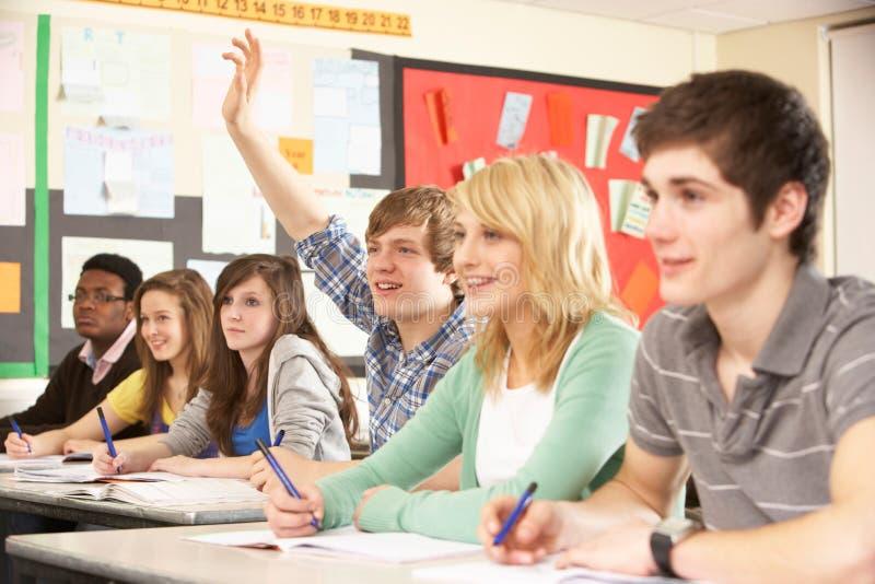 Estudiantes adolescentes que estudian en sala de clase fotos de archivo