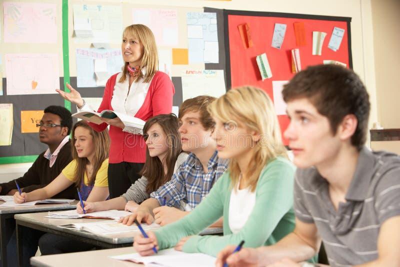 Estudiantes adolescentes que estudian en sala de clase imagen de archivo