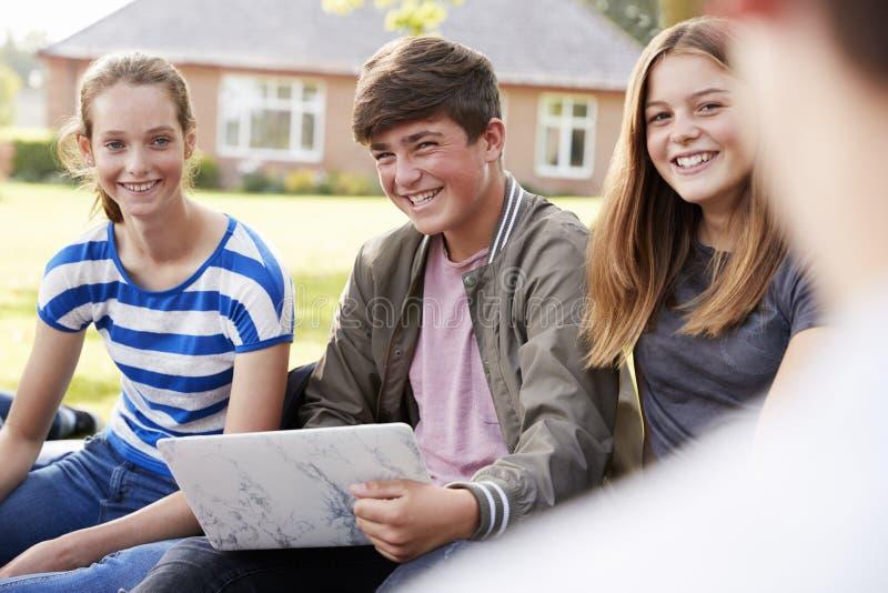 Estudiantes adolescentes que se sientan al aire libre y que trabajan en proyecto foto de archivo libre de regalías