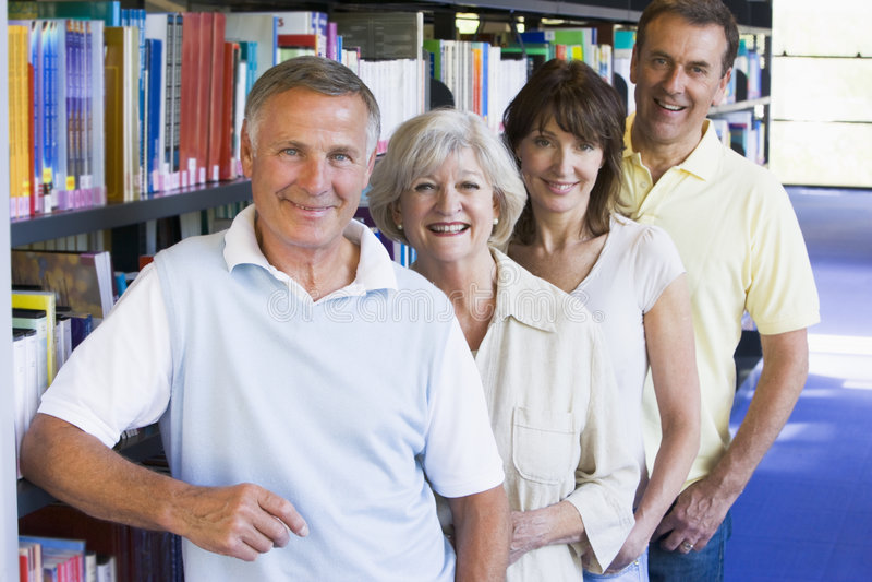 Estudiantes adultos que se colocan en una biblioteca imágenes de archivo libres de regalías