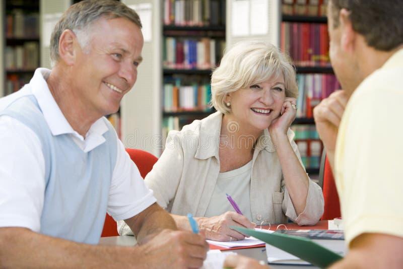 Estudiantes adultos que trabajan junto en una biblioteca imagen de archivo
