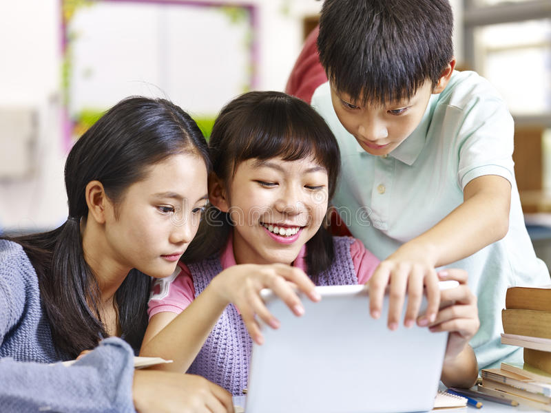 Estudiantes asiáticos de la escuela primaria que usan la tableta en sala de clase imágenes de archivo libres de regalías