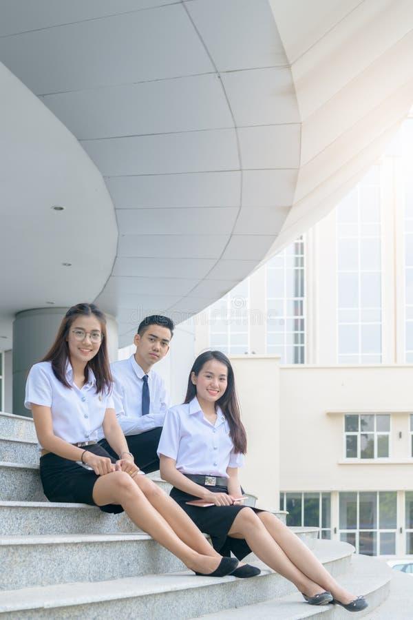 Estudiantes asiáticos felices en el uniforme que localiza en la universidad imagenes de archivo