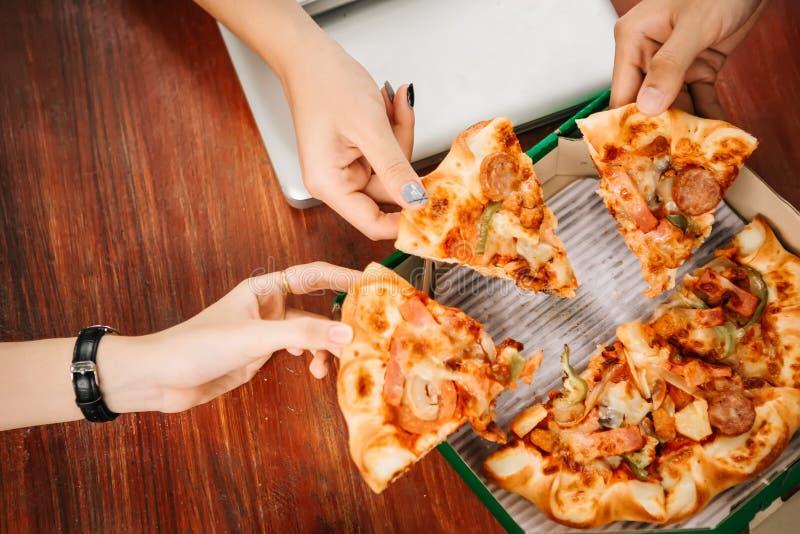 Estudiantes asiáticos que comen comiendo la pizza junta fotos de archivo libres de regalías
