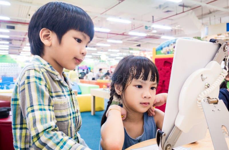 Estudiantes asiáticos que miran el contenido educativo en la tableta fotos de archivo libres de regalías
