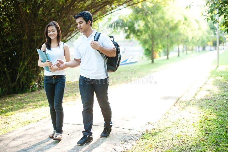 Estudiantes asiáticos que recorren a la universidad fotografía de archivo
