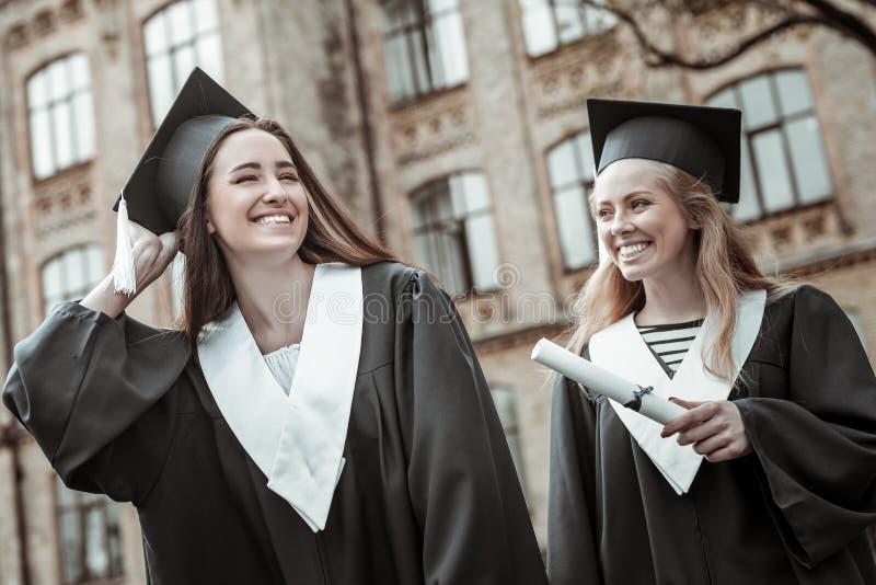 Estudiantes bonitos contentos que llevan el uniforme negro de la graduación foto de archivo libre de regalías
