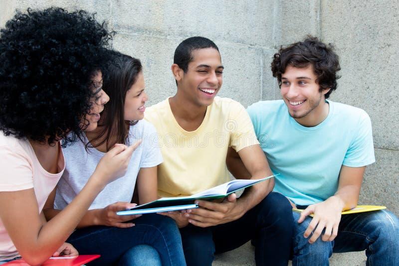 Estudiantes caucásicos y africanos y latinos que aprenden junto imagen de archivo
