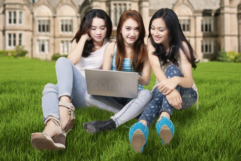 Estudiantes con el ordenador portátil en el patio imágenes de archivo libres de regalías