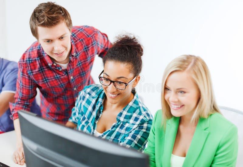 Estudiantes con el ordenador que estudian en la escuela imagen de archivo