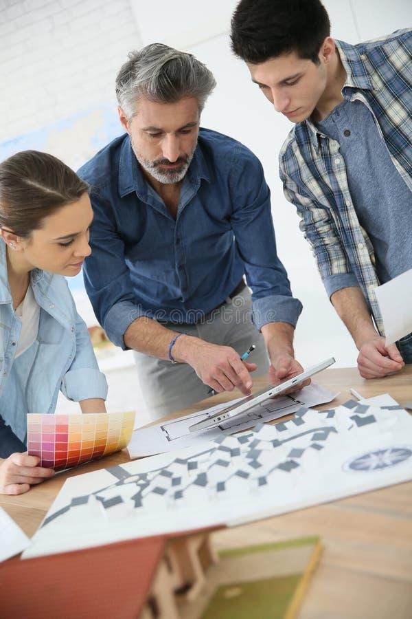 Estudiantes con el profesor que trabaja en proyecto de la arquitectura imagen de archivo