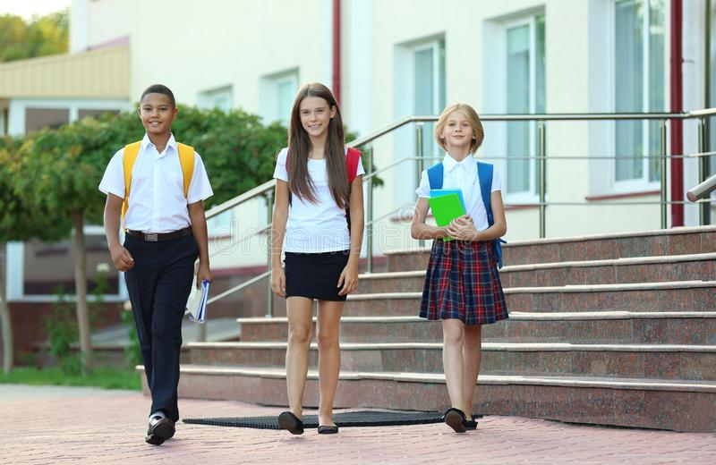 Estudiantes con las mochilas y los cuadernos que caminan en la calle foto de archivo libre de regalías