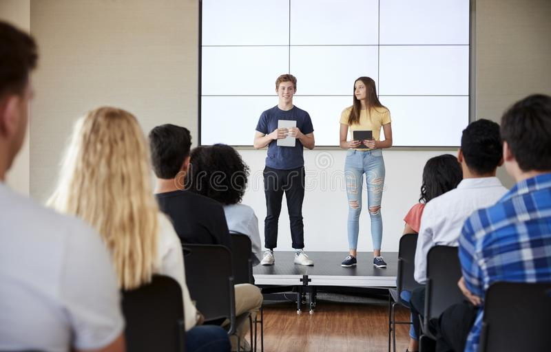 Estudiantes con las tabletas de Digitaces que dan la presentación a la clase de secundaria en Front Of Screen fotografía de archivo libre de regalías