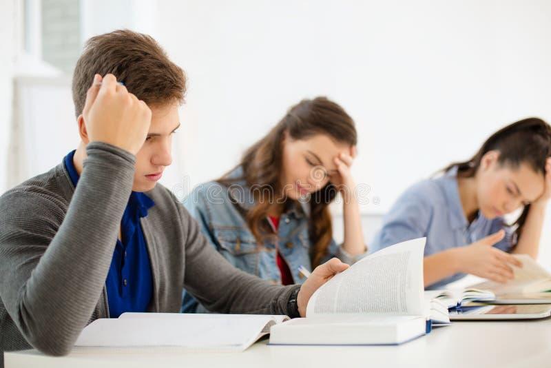 Estudiantes con los cuadernos y PC de la tableta en la escuela imagen de archivo libre de regalías