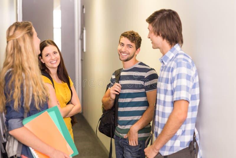 Estudiantes con los ficheros que se colocan en el pasillo de la universidad imagen de archivo libre de regalías