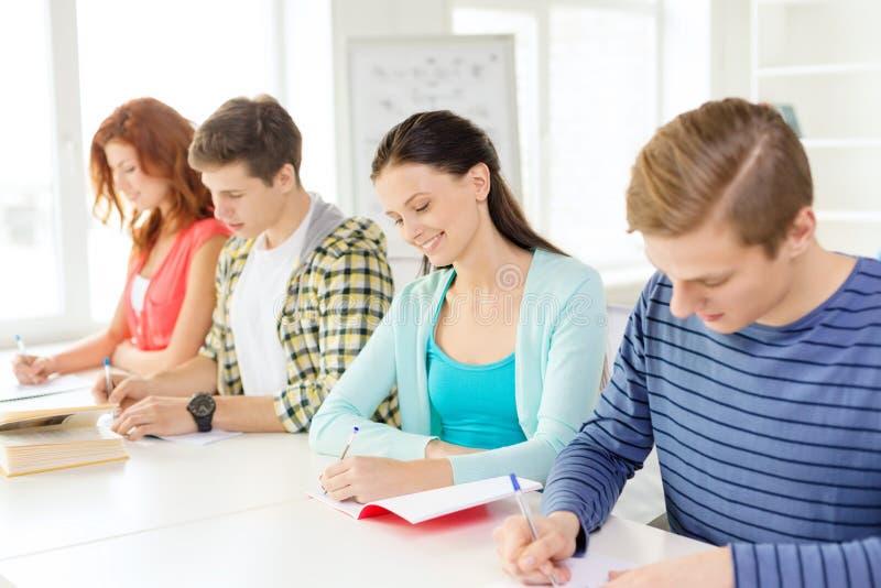 Estudiantes con los libros de texto y los libros en la escuela imagenes de archivo