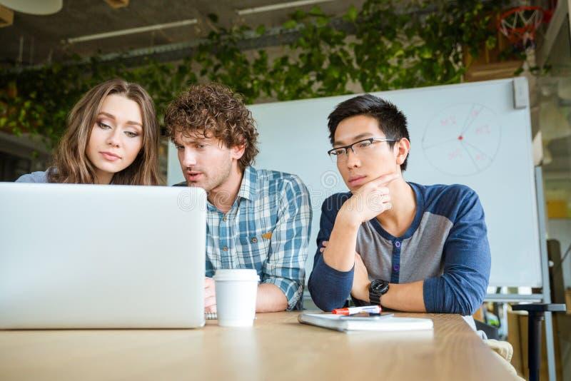 Estudiantes concentrados confiados que aprenden y que estudian con el ordenador portátil fotos de archivo