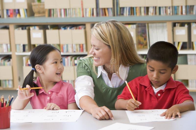 Estudiantes de ayuda del profesor con habilidades de la escritura imagen de archivo