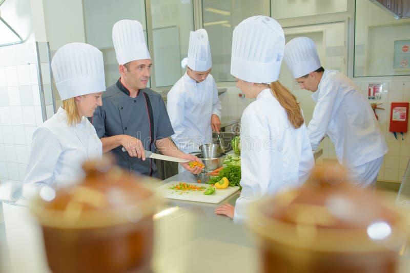 Estudiantes de enseñanza del cocinero en curso de la cocina imagen de archivo libre de regalías