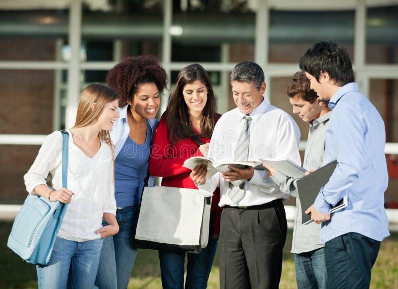 Estudiantes de Explaining Lesson To del profesor en universidad foto de archivo libre de regalías