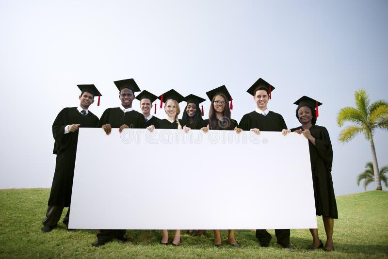 Estudiantes de graduación del grupo al aire libre que llevan a cabo concepto del cartel foto de archivo libre de regalías